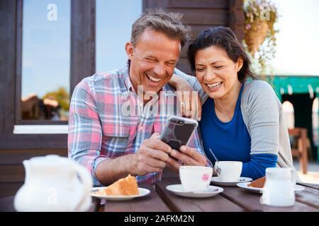 D'âge mûr en centre-Jardin Cafe regarder des images sur téléphone mobile Banque D'Images