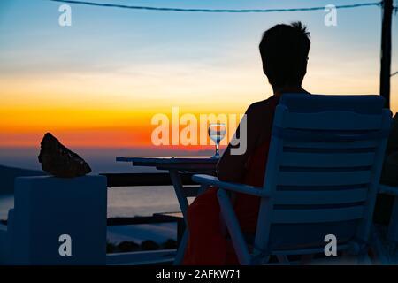 Imerovigli Grèce - 7 août 2019 du lever ou du coucher du soleil intense; concept d'arrière-plan. Large gamme de couleurs, avec la figure silhouette contre le ciel de couleurs et de