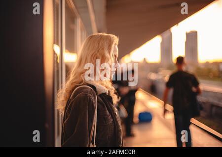 Jeune femme aux cheveux blonds en attente de train à la station de métro