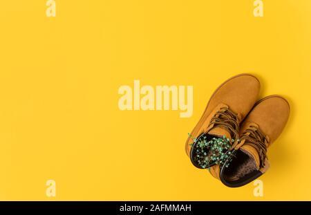 Chaussures d'automne brun avec wildflovers. fond jaune. Banque D'Images