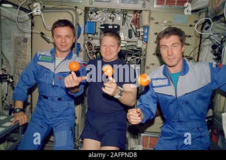 Dans cette image à partir de décembre 2000, l'un des membres de l'équipe de l'expédition -- la première à habiter en permanence la Station spatiale internationale -- sont sur le point de manger un festin d'oranges fraîches à bord du module de service Zvezda. Sur la photo, de gauche à droite, sont commandant de Soyouz Youri Gidzenko P., commandant de Station William M. Shepherd et le cosmonaute Sergei K. Krikalev. Depuis 19 ans et plus, la station a fonctionné comme un partenariat international qui est autant un accomplissement humain tel qu'il est technologique et un exercice de la meilleure façon de planifier, coordonner et suivre les diverses activités du programme de l'organi Banque D'Images