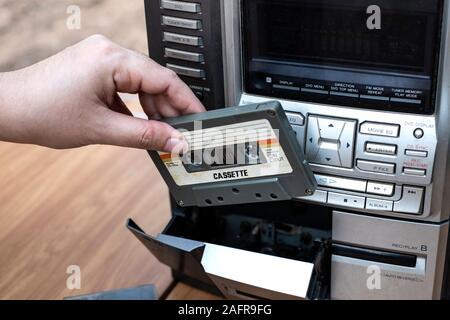 Mettre la main des femmes en cassette audio à l'ancienne sur le dessus du lecteur de bureau wood background