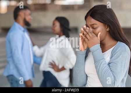Jeune fille pleurer en regardant son ex petit ami heureux avec une autre femme Banque D'Images