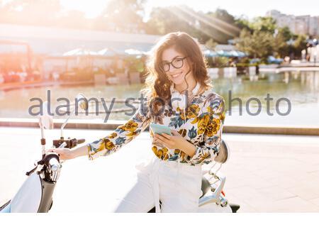 Belle Dame brune portant tailleur-pantalon blanc élégant et grand assis sur casque scooter et à la recherche avec sourire timide. Portrait de jeune fille en plein air à la mode dans le vêtement élégant près de refroidissement. fontaine ville Banque D'Images