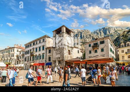 Les touristes visiter, dîner dans des cafés et boutique sous la tour de l'horloge à la place des bras, dans la ville médiévale fortifiée de Kotor, Monténégro Banque D'Images
