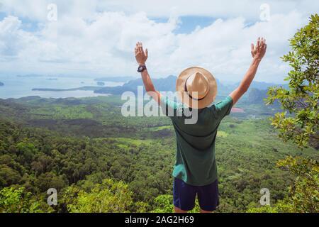 Image: un happy traveler avec ses mains posées jusqu'à l'admiration se dresse au sommet de la haute montagne et les montres paysage de forêt, colline, et la mer.