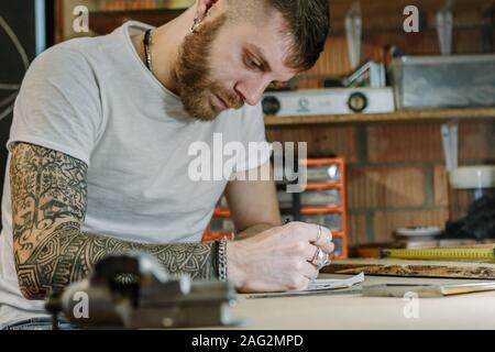 L'artiste artisan créateur d'un nouveau produit en bois dans son atelier à domicile. L'homme au travail sur bois concept Banque D'Images