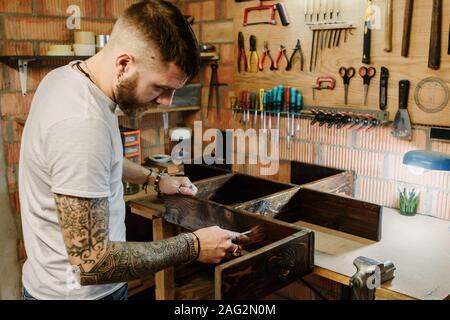 Jeune designer bois vernis appliquer la peinture sur un meuble en bois à l'atelier d'artisanat Banque D'Images