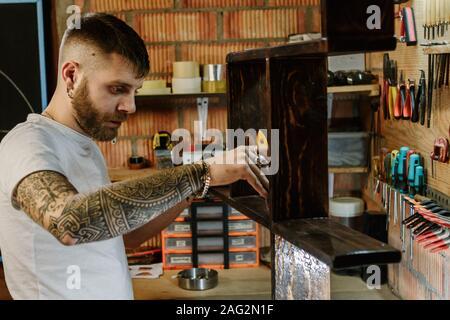 Artiste Artisan tenant un pinceau et de l'application de peinture vernis sur un meuble en bois à l'atelier d'artisanat Banque D'Images