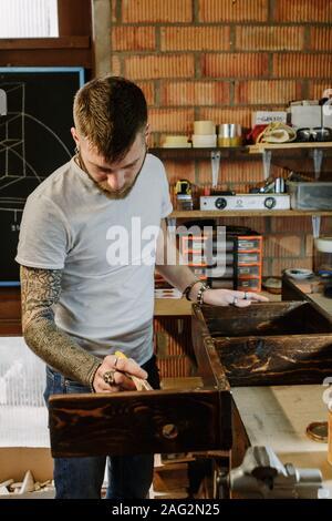 Artiste tatoué appliquant le vernis de la peinture sur un meuble en bois à l'atelier d'artisanat Banque D'Images