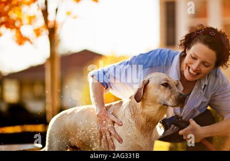 Mid-adult woman giving son chien le tuyau dans l'arrière-cour. Banque D'Images
