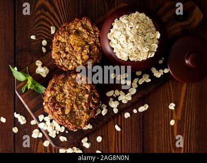 Biscuits à la maison avec la banane, l'avoine, les noix, les œufs et la farine gratuitement sur une table en bois foncé marron, vue du dessus. Banque D'Images