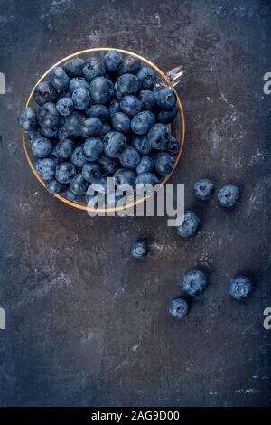 Bleuets frais dans un bol en verre sur fond sombre, vue du dessus