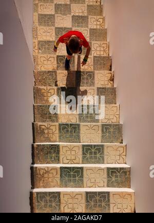 Un jeune garçon dans un maillot de l'équipe de soccer national espagnol de style mauresque, escalade, sol carrelé étapes de Nerja. Costa del Sol, la province de Malaga, Andalousie, Espagne Banque D'Images