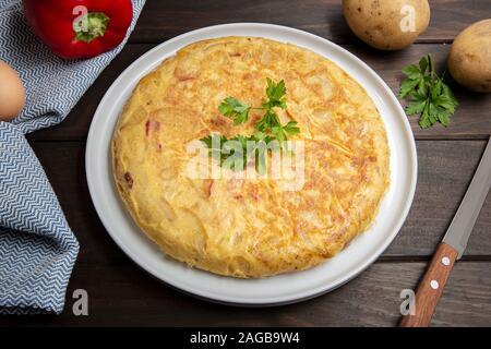 Omelette Espagnole tortilla espagnol appelé. Recette omelette aux pommes de terre, l'oeuf, l'oignon et le poivron rouge Banque D'Images