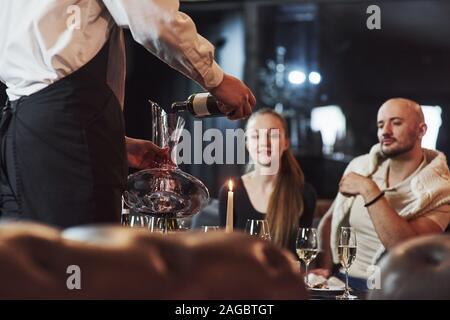 Processus de verser le vin. Fille avec son petit ami ont de belles soirée au restaurant magnifique Banque D'Images