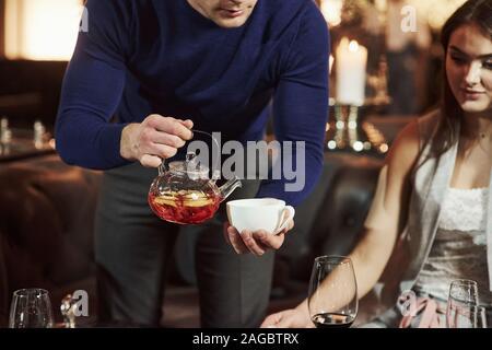 L'homme penché plateau en blanc cup. Amis de la famille avoir beau temps dans un beau restaurant moderne de luxe