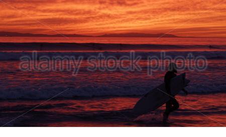 La silhouette d'un surfeur marche à travers la côte de l'océan couverts avec les couleurs du coucher de soleil Banque D'Images