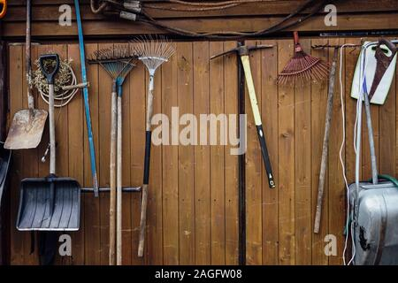 Râteaux pelles marteaux hanging on wooden wall