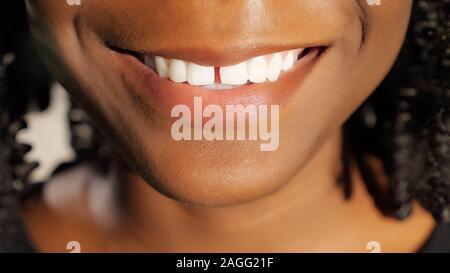 Jolie jeune femme africaine avec des cheveux noirs frisés sourire montrant des dents blanches closeup