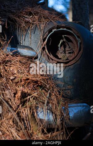 Un vieux phare auto rouillée socket sur une voiture couverte de paille de pin. Banque D'Images