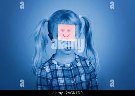 Triste Malheureux Caucasian preschool girl avec drôle note adhésive rose sur son visage. Kid: exprimer des sentiments. Des difficultés, des problèmes de l'enfant Banque D'Images