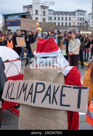 """Erfurt, Allemagne. 18Th Oct, 2019. Un participant d'un vêtu Christmassy vendredi pour les futurs """"light demo' sous la devise """"Une lumière dans l'obscurité - climate justice now!' est porteur d'une affiche avec les mots """"climat"""" sur le dos. Avec cette campagne, les étudiants et les participants sont également retour sur une année de vendredi pour l'avenir d'Erfurt. Crédit: Michael Reichel/dpa-Zentralbild/dpa/Alamy Live News Banque D'Images"""