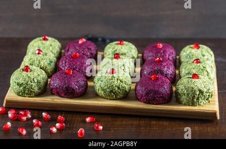Pkhali de betteraves et haricots sur une planche à découper sur un fond de bois sombre. Plat de légumes traditionnels géorgiens, noix et d'épices. Banque D'Images