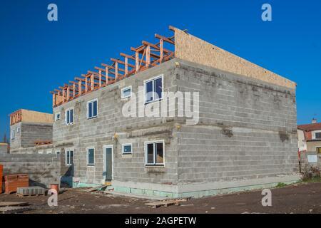 Maison en construction. Juste après l'instalation de panneaux sur le toit. Planches en bois et panneaux de bois pressé.