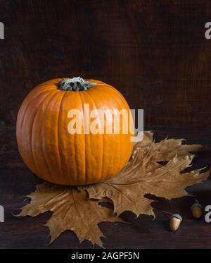 Composition d'automne. Citrouille, feuilles mortes, glands sur un fond de bois sombre. L'automne fête de l'arrière-plan. Concept de l'automne. Banque D'Images