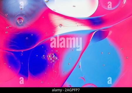 Résumé fond coloré. Rose bleu cercles blancs, et l'huile bulles dans l'eau close up. L'abstraction Macro. La texture de l'huile et le motif arc-en-ciel. Banque D'Images