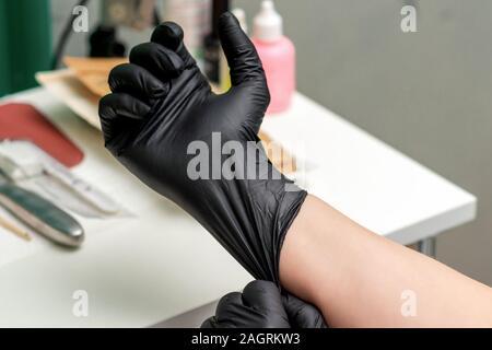 Gants noirs en latex médical sur main de l'infirmière ou esthéticienne, Close up. Banque D'Images