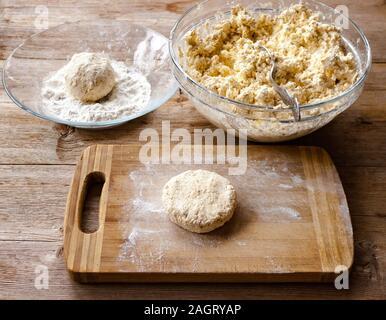 Un petit-déjeuner traditionnel russe syrniki cru cru crêpes de fromage cottage sur la vieille planche à découper en bois historique vue en gros plan. Soft focus sélectif. Banque D'Images