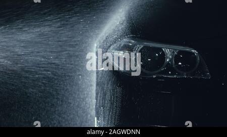 Phare de voiture lavage. Corps de véhicules modernes de Lavage par jet haute pression laver l'eau. flexible Auto Glass, projecteur angel eyes en gouttes. Banque D'Images