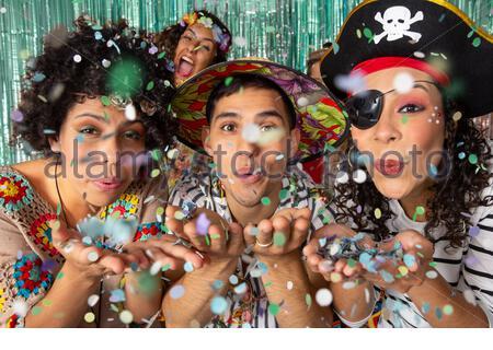Habillé Amis brésiliens faisant partie dans la nuit. Les gens blowing confetti. Trois personnes regardent l'appareil photo avec leurs mains à l'avant. Carnaval à B Banque D'Images