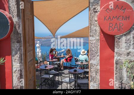 Santorini Grèce - le 8 août 2019; les touristes s'asseoir à des tables de bar donnant sur bay ci-dessous enjoying view nos îles et de navire de croisière et des boissons fraîches.