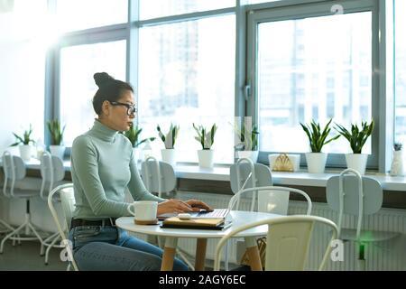 Étudiante sérieuse en casualwear assis par table en face de l'ordinateur portable tout en se concentrant sur le réseau dans le cafe