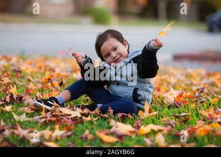 Jeune garçon portant une veste de letterman qui est assis dans la cour avant, rempli de jaune et rouge les feuilles d'automne. Banque D'Images