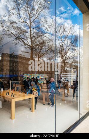 Paris, France - Mar 19, 2019 - Vue depuis la rue de personnes à l'intérieur d'admirer les derniers smartphones et ordinateurs vitrine en verre de l'emblématique Apple Store sur les Champs Elysées Banque D'Images