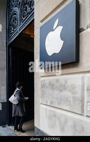 Paris, France - Mar 19, 2019: femme entre dans le magasin avec les ordinateurs Apple logo insigne à côté de l'entrée de l'emblématique Apple Store sur les Champs Elysées - tilt shift de l'objectif utilisé Banque D'Images