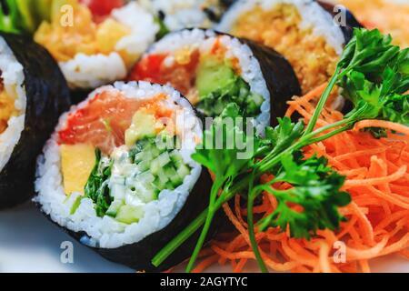 Sushi maki varié avec le concombre, la carotte, le persil, le coréen le chou de mer et le saumon maki. Rouleaux de sushi sashimi japonais avec des oeufs de saumon en gros plan photo Banque D'Images