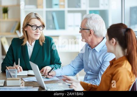 Femme mature à lunettes de parler à ses collègues et ils discuter de plan d'affaires à la table de réunion d'affaires Banque D'Images