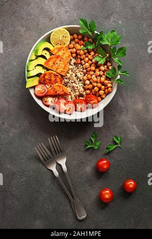 Un bol de salade végétalienne saine, poêlée de pois chiches, beignets de patate douce, d'avocat, quinoa, tomates et les verts. Haut de la vue, télévision lay Banque D'Images