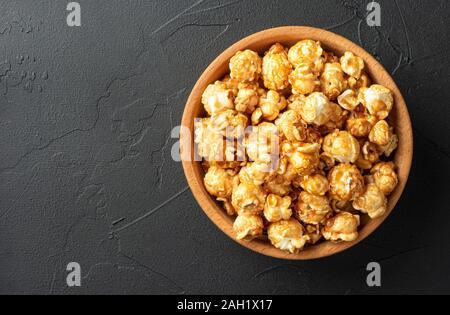 Maïs soufflé au caramel bol en bois sur fond sombre Banque D'Images
