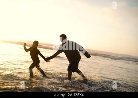 Le père et le jeune fils de jouer dans l'océan. Banque D'Images