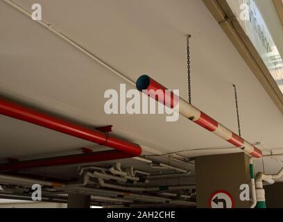 Limitation de hauteur de voiture Gros plan signe fait à partir de tuyaux de PVC peintes en rouge et blanc, suspendu au plafond par des chaînes à l'entrée du stationnement Banque D'Images