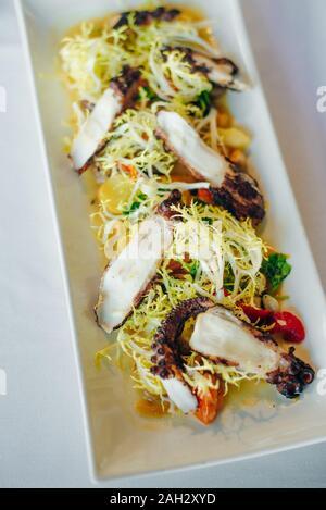 Octopus carbonisé avec des légumes et de la salade au restaurant Banque D'Images