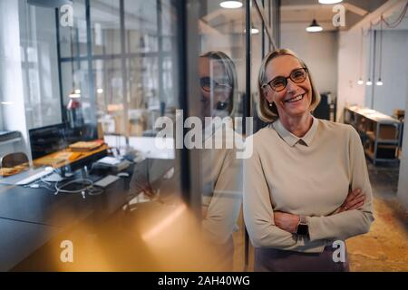 Portrait of smiling mature woman leaning against vitre in office Banque D'Images