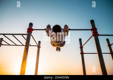 Jeune homme pratiquant la gymnastique à un sport en plein air au lever du soleil