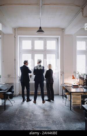 Les gens d'affaires debout à la fenêtre in office